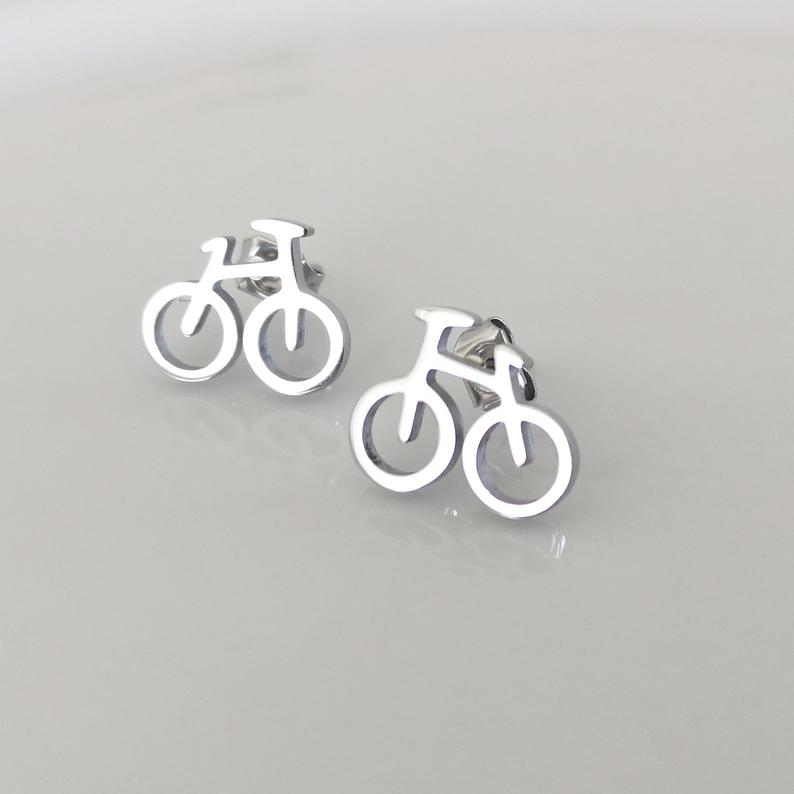 A pair of bicycle earrings are on the table.