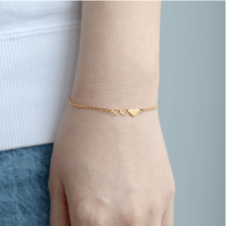 This is a gold tiny three heart bracelet.